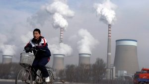 A Chinese boy cycles past a cooling towers of a coal-fired power plant in Dadong, Shanxi province, China,Dec. 3, 2009. (AP / Andy Wong, File)