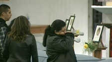 Mourners cry over the casket of a worker killed in a crash in Hampstead, Ont. during a memorial service, Wednesday, Feb. 15, 2012.