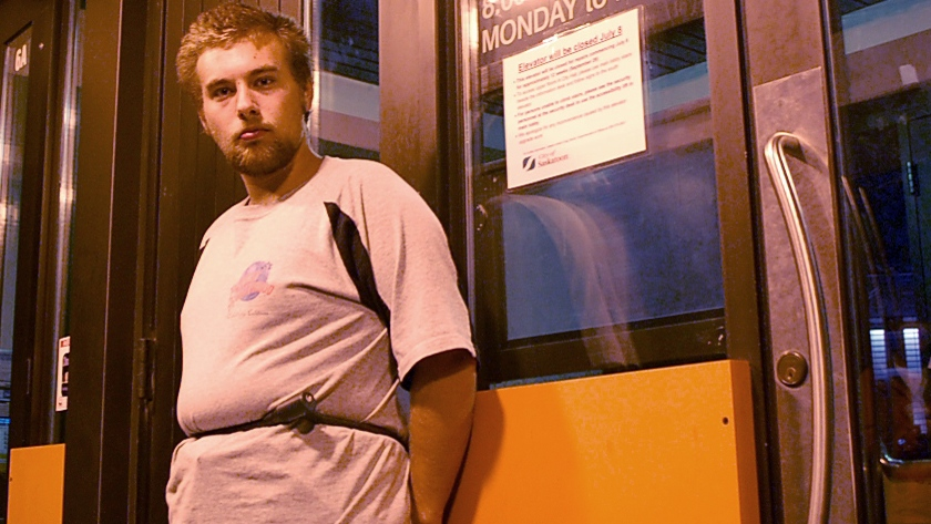 Dailen Yackobeck, 18, stands chained to Saskatoon City Hall doors Sept. 20, 2014 in protest of a transit lockout.