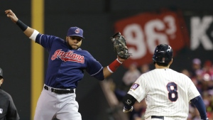 Cleveland Indians first baseman Carlos Santana, left, jumps to take the throw from shortstop Jose Ramirez before tagging out Minnesota Twins' Kurt Suzuki in the fourth inning of a baseball game in Minneapolis, Saturday, Sept. 20, 2014. (AP / Jim Mone)
