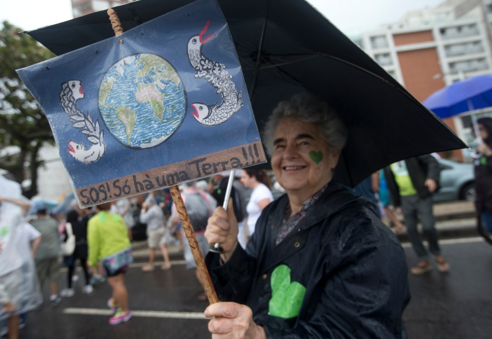 A woman holds a sign that reads in Portuguese 'SOS, There is only one Earth,' during the People's Climate March at Ipanema beach, Rio de Janeiro, Brazil on Sunday, Sept. 21, 2014. (AP / Silvia Izquierdo)