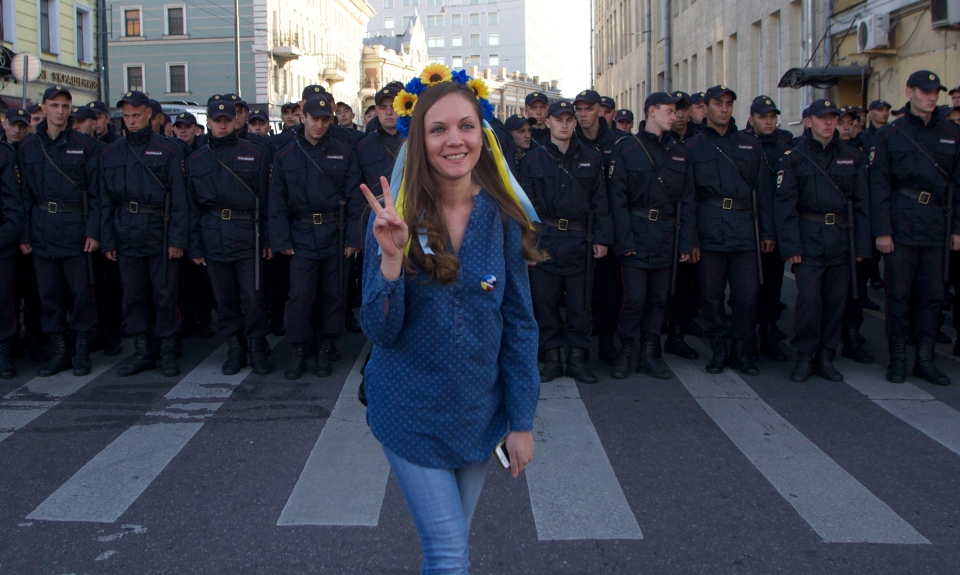 A woman wearing traditional Ukrainian flower headband poses for a photo in front of police officers during an anti-war rally in downtown Moscow, Russia on Sunday, Sept. 21, 2014. Thousands of people were marching through central Moscow to demonstrate against the fighting in Ukraine. (AP / Denis Tyrin)