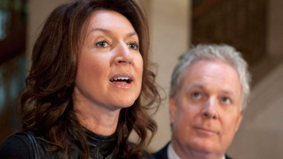 Nathalie Normandeau announces her resignation as deputy premier of Quebec as Jean Charest looks on, Sept. 6, 2011. (THE CANADIAN PRESS / Jacques Boissinot)