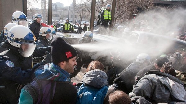 Police use pepper spray to disperse a crowd blocking the Delta hotel during a demonstration against higher tuition fees Thursday, February 16, 2012 in Montreal.THE CANADIAN PRESS/Ryan Remiorz