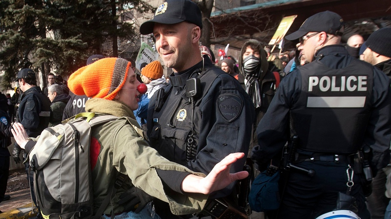 A protester tries to block a police officer during a demonstration against higher tuition fees Thursday, February 16, 2012 in Montreal.THE CANADIAN PRESS/Ryan Remiorz