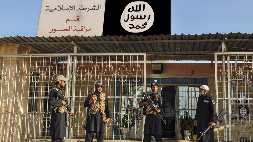 This undated file photo posted on a militant website Friday, Sept. 19, 2014, shows Islamic State group policemen standing guard in front of a police station in Nineveh province, Iraq.  (AP via militant website)