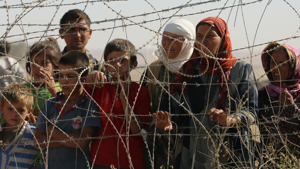 A family stand near a fence as several hundred Syrian refugees wait to cross into Turkey at the border in Suruc, Turkey, Sunday, Sept. 21, 2014. (AP / Burhan Ozbilici)