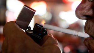 In this June 11, 2009 photo, a customer at the Red Key Taven in Indianapolis lights a cigarette. (AP Photo/Darron Cummings)