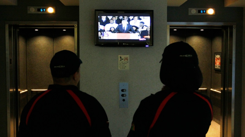 Concession workers at the United Center, watch actor Kevin Costner eulogize Whitney Houston before an NBA basketball game between the Chicago Bulls and the New Jersey Nets, Saturday, Feb. 18, 2012, in Chicago. (AP / Charles Rex Arbogast)