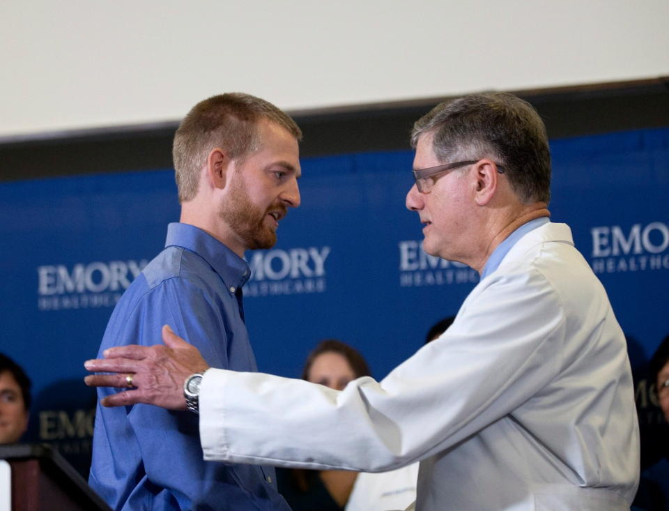 Ebola victim Dr. Kent Brantly, left, embraces Dr. Bruce Ribner, medical director of Emory's Infectious Disease Unit, after being released from Emory University Hospital in Atlanta, Thursday, Aug. 21, 2014. (AP / John Bazemore)