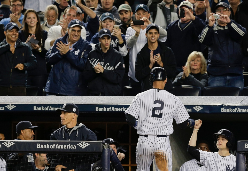 New York Yankees' Derek Jeter is greeted by teammates and applauded by fans as he enters the dugout after scoring against the Baltimore Orioles in the first inning a baseball game, Thursday, Sept. 25, 2014, in New York. (AP Photo/Julie Jacobson)