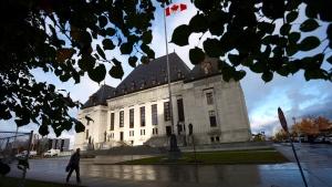 A pedestrian walks past the Supreme Court of Canada in Ottawa, Oct. 18, 2013. (Sean Kilpatrick / THE CANADIAN PRESS)