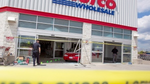 Police investigate after a car backed through the entrance of Costco in London, Ont., on July 25, 2014. (Geoff Robins / THE CANADIAN PRESS)