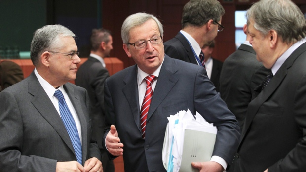 Greek Prime Minister Lucas Papademos, left, speaks with Luxembourg's Prime Minister Jean-Claude Juncker, centre, and Greek Finance Minister Evangelos Venizelos, right, during a round table meeting of eurozone finance ministers at the EU Council building in Brussels on Monday, Feb. 20, 2012. (AP / Yves Logghe)