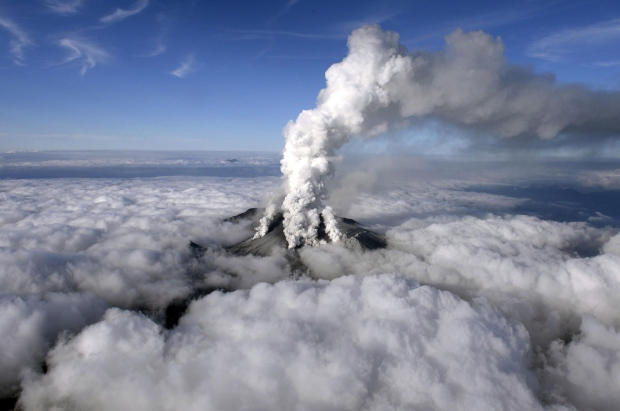 Dense white plumes rise high in the air as Mt. Ontake erupts in central Japan, Saturday, Sept. 27, 2014. (AP / Kyodo News)