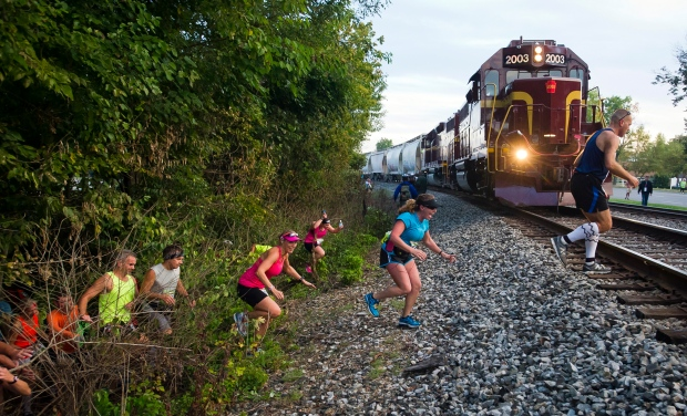 Runners in a Columbus, Indiana marathon come out of the woods and are surprised by a Louisville & Indiana train, Saturday, Sept. 27, 2014. (AP/The Republic, Andrew Laker)