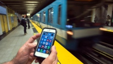 A commuter in Montreal looks at his smart phone