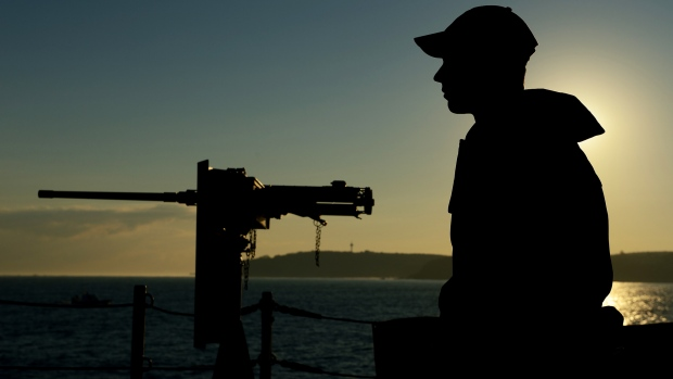 As the sun rises a member of the ship's company on board HMCS Toronto provides force protection while transiting through the Bosphorus Strait during Operation Reassurance on Sept. 25, 2014. (Sgt. Matthew McGregor / Canadian Forces Combat Camera)
