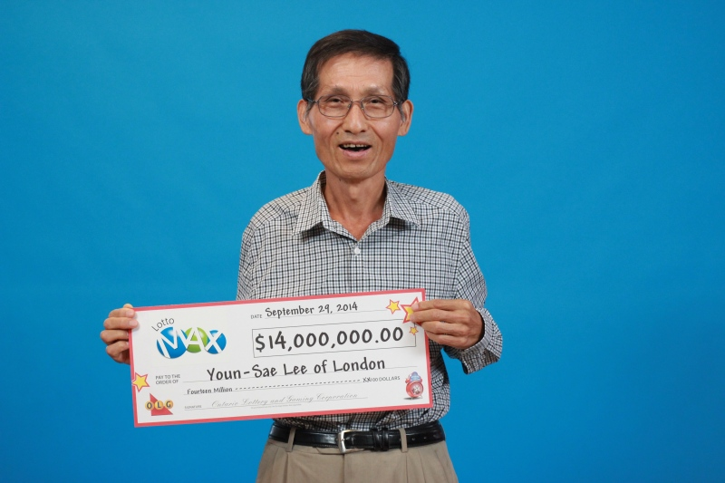 London Lotto Max winner Youn-Sae Lee picks up his cheque for $14 million at the OLG Prize Centre in Toronto.