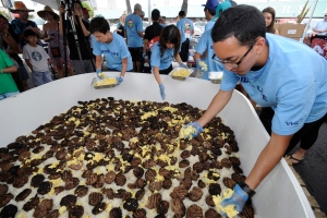 Yutaro Kondo, right, adds handfuls of scrambled eggs on top of a layer of beef patties and rice on the giant Loco Moco in Honolulu, Hawaii on Sunday, Sept. 28, 2014. (AP Photo/Honolulu Star-Advertiser, Bruce Asato)