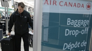 An Air Canada passenger prepares to drop off his baggage at Vancouver International Airport in Richmond, B.C., on Tuesday, June 17, 2008. (Darryl Dyck / THE CANADIAN PRESS)