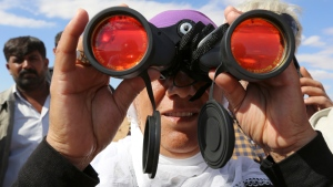 A Turkish Kurdish woman uses binoculars to watch the fighting between Islamic militants and Kurdish forces to the west of Kobani, Syria. (AP / Burhan Ozbilici)