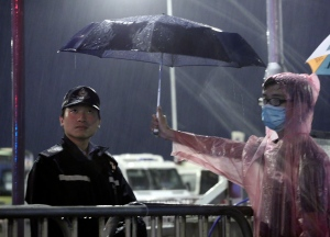 A young pro-democracy demonstrator holds an umbrella for a police officer during a demonstration in Hong Kong on Tuesday, Sept. 30, 2014. (AP / Apple Daily)