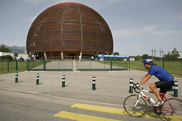 A cyclist passes by the wooden 'Globe' at the entrance of the European Organization for Nuclear Research, CERN, near Geneva, Switzerland, Tuesday, Sept. 9, 2008. Scientists will fire up the biggest physics experiment in history at CERN Sept. 10, 2008 when they hope to detect evidence of extra dimensions, invisible 'dark matter' and an elusive particle called the Higgs boson.(AP Photo/Anja Niedringhaus)