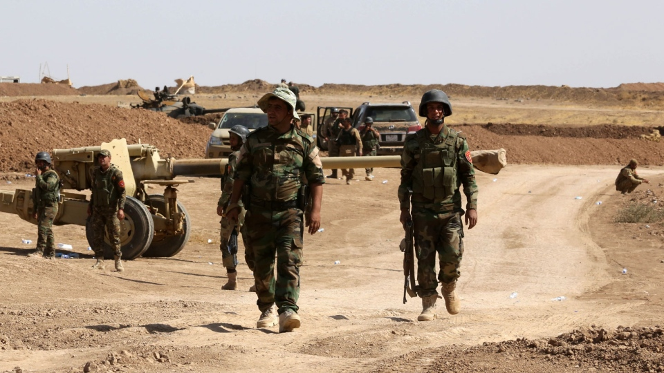 Kurdish peshmerga forces stand by their vehicles in Mahmoudiyah, Iraq, a day after they take control of the village from the Islamic State group, as they patrol on Wednesday, Oct. 1, 2014. (AP / Hadi Mizban)
