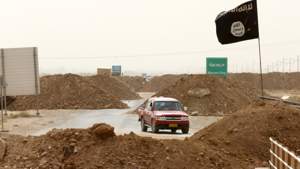 Islamic State militants pass a checkpoint bearing the group's trademark black flag in the village of Maryam Begg in Kirkuk, 290 kilometres north of Baghdad, Iraq, Monday, Sept. 29, 2014. (AP / Hadi Mizban)