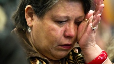 Residential school survivor Kim Good, of the Snuneymuxw First Nation near Nanaimo, B.C., wipes away tears as she listens to Truth and Reconciliation Commission Chair, Justice Murray Sinclair release the commission's interim report during a news conference in Vancouver, B.C., on Friday, Feb. 24, 2012. (Darryl Dyck / THE CANADIAN PRESS)
