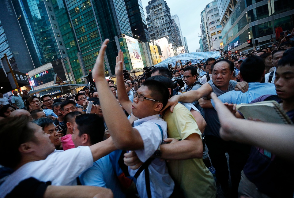 A pro-government supporter tries to grab on to a student pro-democracy activist as policeman were escorting him out of the tent, in Kowloon's crowded Mong Kok district, Hong Kong, Friday, Oct. 3, 2014. (AP / Wong Maye-E)