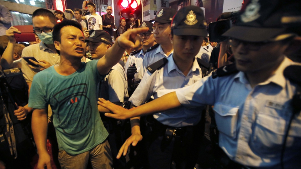 Police hold back local residents demanding pro-democracy student protesters to leave their occupied roads in Mong Kok, Hong Kong, Friday, Oct. 3, 2014. (AP / Wally Santana)