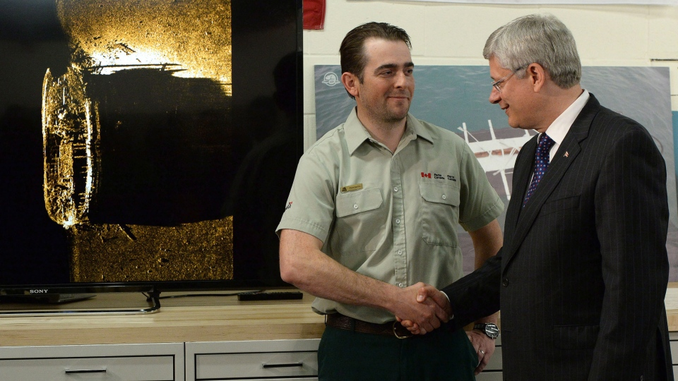 Prime Minister Stephen Harper shakes hands with Parks Canada's expedition leader Ryan Harris looks in Ottawa on Tuesday September 9, 2014. (Sean Kilpatrick / THE CANADIAN PRESS)