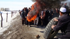 Afghans burn tires during an anti-U.S. demonstration over burning of Qur'ans at a U.S. military base, in Muhammad Agha, Logar province south of Kabul, Afghanistan, Saturday, Feb. 25, 2012.