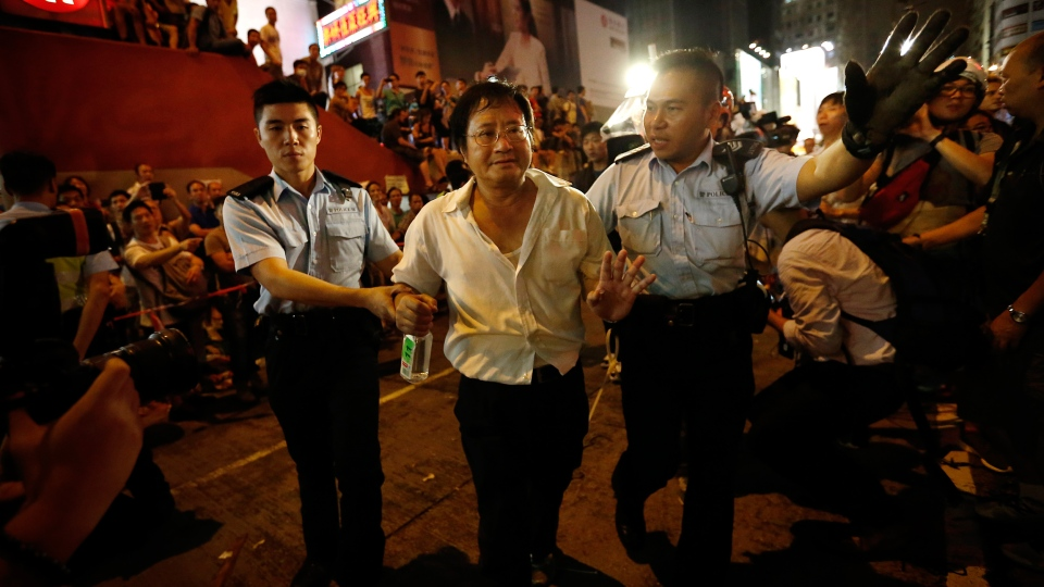 Local police take a man away from the confrontation of pro-democracy student protesters and angry local residents in Kowloon's crowded Mong Kok district, Saturday, Oct. 4, 2014 in Hong Kong. (AP / Wong Maye-E)