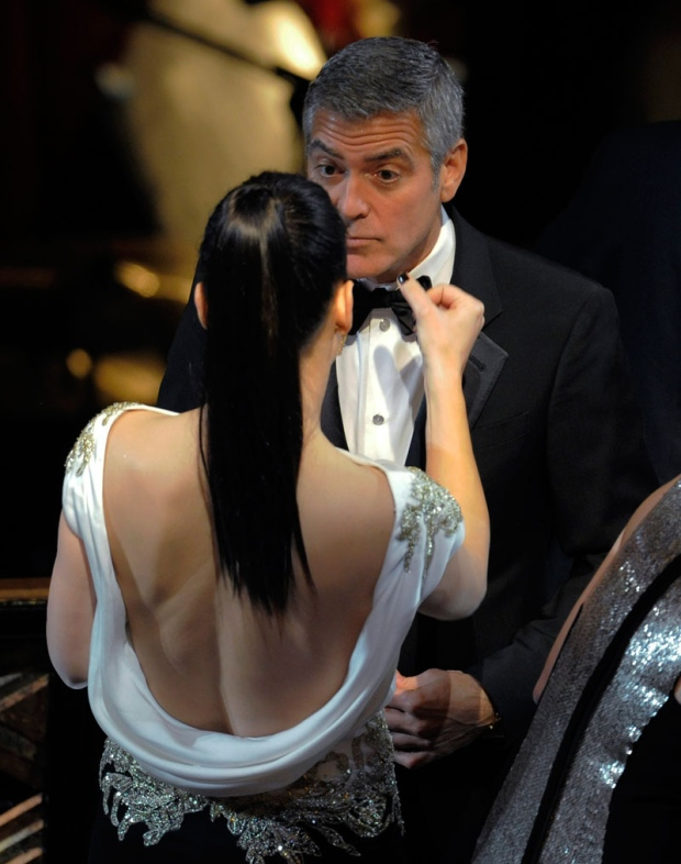 Sandra Bullock wipes the face of George Clooney before the 84th Academy Awards show on Sunday, Feb. 26, 2012, in the Hollywood section of Los Angeles. (AP Photo/Mark J. Terrill)