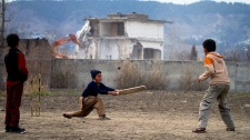 Pakistani youngsters play cricket near the compound, centre back, of Osama bin Laden which is demolishing by authorities in Abbottabad, Pakistan on Sunday, Feb. 26, 2012.