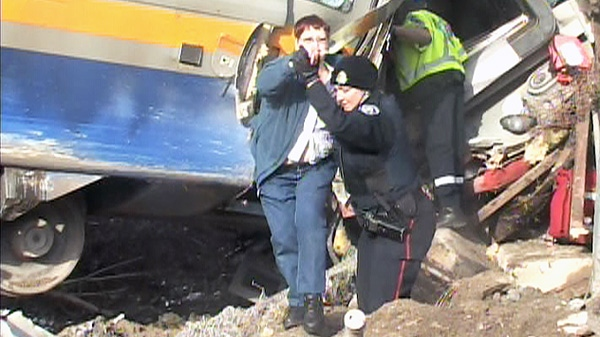 Emergency officials help a passenger from the wreckage of a Via Rail train that derailed in Burlington, Ont. on Sunday, Feb. 26, 2012.