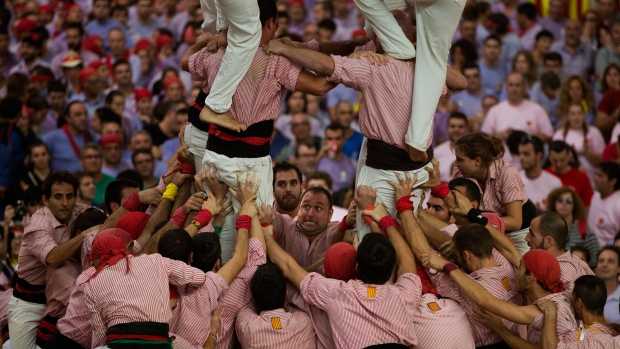 Members of the Castellers de Tarragona work together making their human tower during the 25th Human Tower Competition in Tarragona, Spain, on Sunday, Oct. 5, 2014. (AP / Emilio Morenatti)