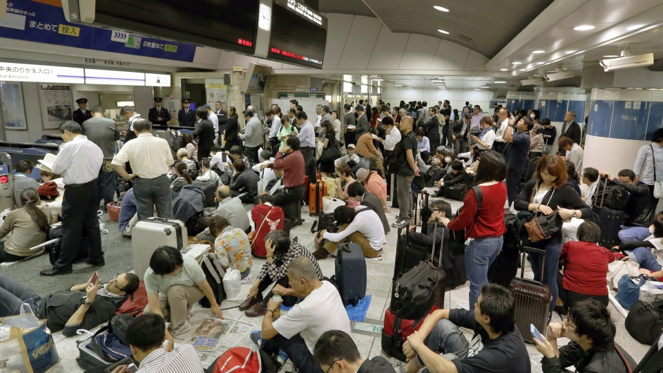 Passengers wait for the resumption of bullet train service at Tokyo Station in Tokyo Monday, Oct. 6, 2014. (AP / Kyodo News)