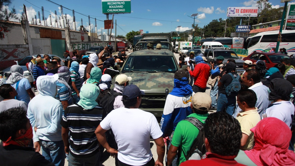 Students and relatives of missing students surround and deny access to a convoy of military vehicles as they block a main highway in the city of Chilpancingo, Mexico, Sunday Oct. 5, 2014. (AP / Felix Marquez)