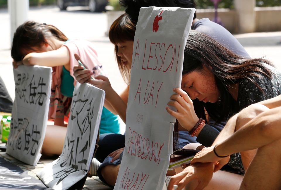 Pro-democracy student protesters show their placards at the Chinese University of Hong Kong campus to urge students to boycott classes, Monday, Oct. 6, 2014. (AP / Kin Cheung)