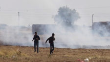 Kurdish youth run from tear gas near Suruc