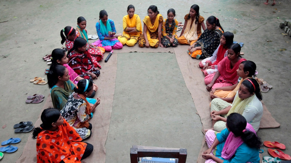 A group of Bangladeshi girls, aged between 12 and 17, hold courtyard meeting to learn about menstruation, reproductive health, HIV/AIDS and use of contraceptives at Saghata, a remote impoverished farming village in Gaibandha district, Bangladesh, Sept. 30, 2012. (AP / A.M. Ahad)