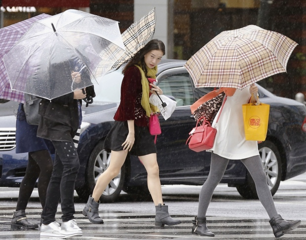 Pedestrians make their way through a street in Tokyo while a powerful typhoon approaches Tokyo, Monday, Oct. 6, 2014. (Kyodo News)