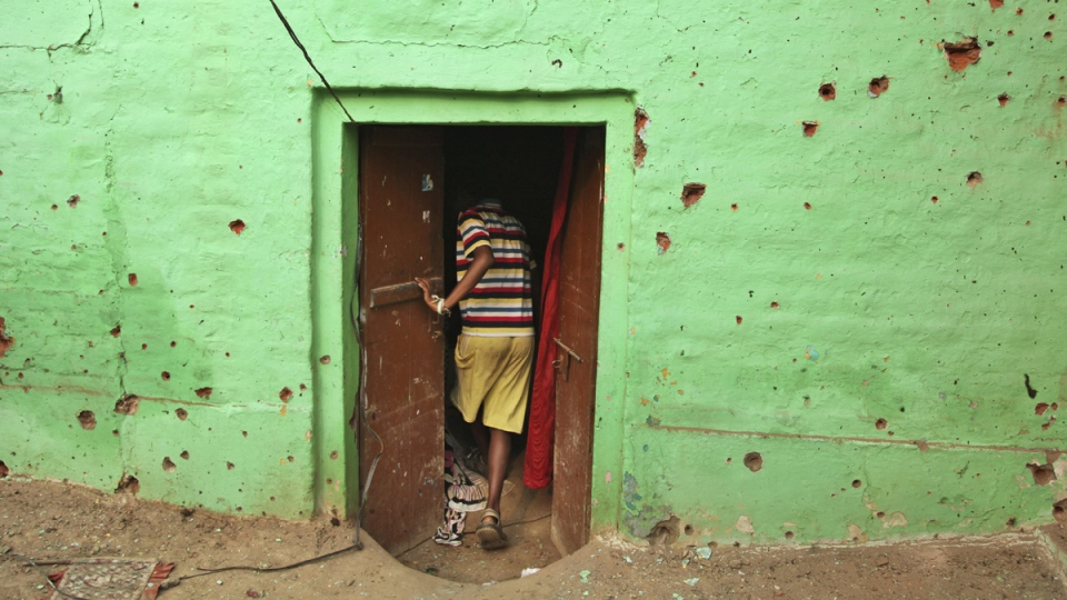 An Indian villager enters a door of his residence near mortar shell marks allegedly fired from the Pakistan's side at Masha da kothe village, in Arnia Sector near the India-Pakistan international border, about 47 kilometres from Jammu, India, Monday, Oct. 6, 2014. (AP / Channi Anand)