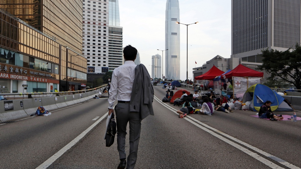 A man walks to work as the pro-democracy student protesters sleep on a roadside in the occupied areas surrounding the government complex in Hong Kong, Monday, Oct. 6, 2014. (AP / Kin Cheung)