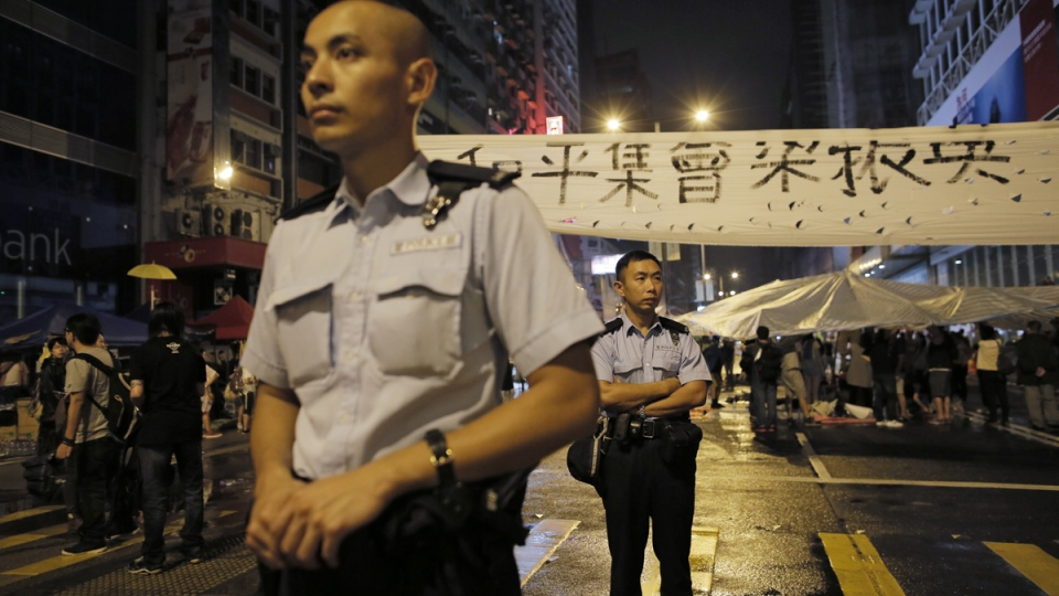 Police officers stand guard at an intersection on a main road occupied by protesters in the Mong Kok area in Hong Kong, early Tuesday, Oct. 7, 2014. (AP / Vincent Yu)