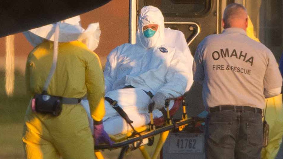 Ashoka Mukpo is loaded into an ambulance, Monday Oct. 6, 2014, after arriving in Omaha, Neb. (The World-Herald /  James R. Burnett)